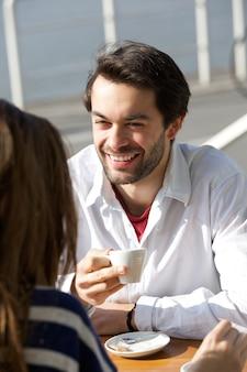 Jovem feliz bebendo café com mulher