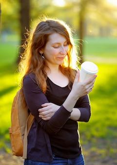 Jovem feliz bebendo café ou chá ao ar livre