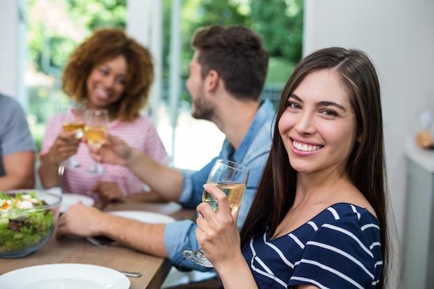 Jovem feliz bebendo vinho com os amigos