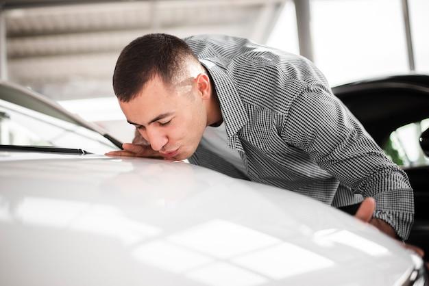 Jovem feliz beijando seu carro novo