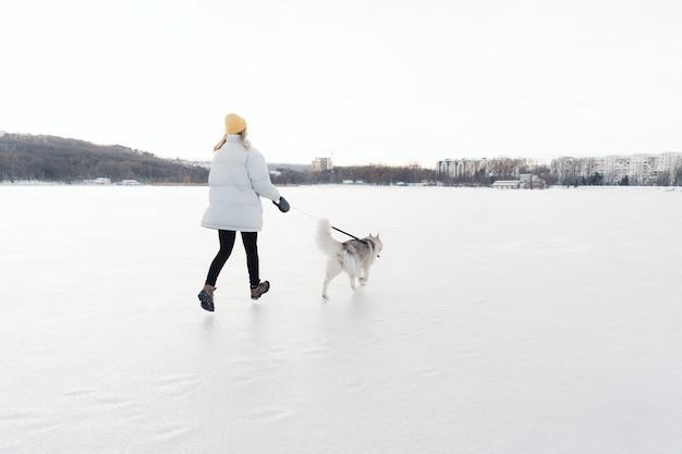 Jovem feliz brincando com cachorro husky siberiano em winter park