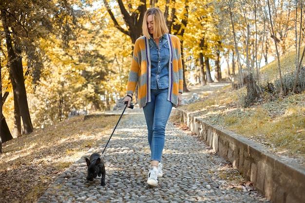 Jovem feliz caminhando com o buldogue francês ao ar livre no outono