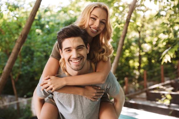 Jovem feliz carregando sua linda namorada nas costas