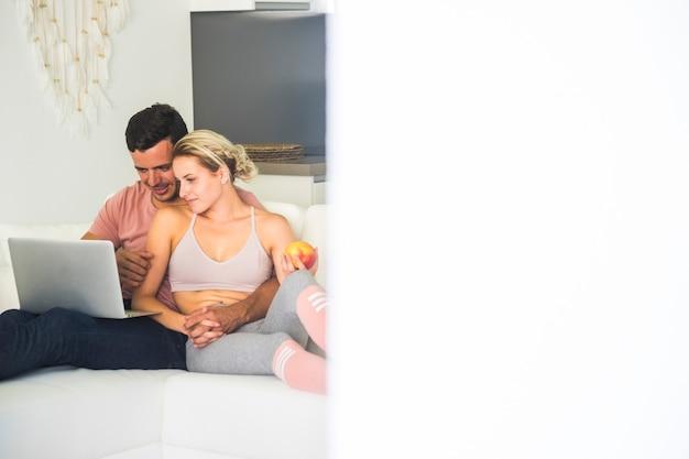 Jovem feliz casal caucasianos em casa com laptop pessoal e conexão à internet - juntos em atividades de lazer internas com tecnologia, sentados no sofá e sorrindo