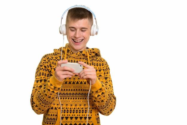 Jovem feliz caucasiano sorrindo enquanto brincava com o celular