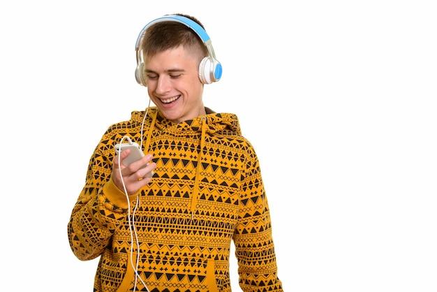 Jovem feliz caucasiano sorrindo enquanto usa o celular e ouve música