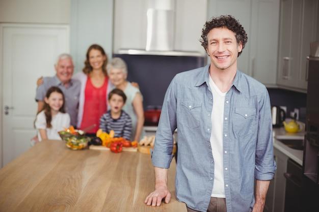 Jovem feliz com a família na cozinha