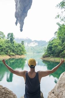 Jovem feliz com as mãos levantar-se no belo lago, paisagem de montanha com belas clo
