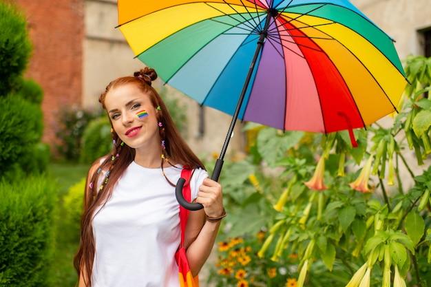 Jovem feliz com bandeira lgbt no rosto, posando com guarda-chuva de arco-íris
