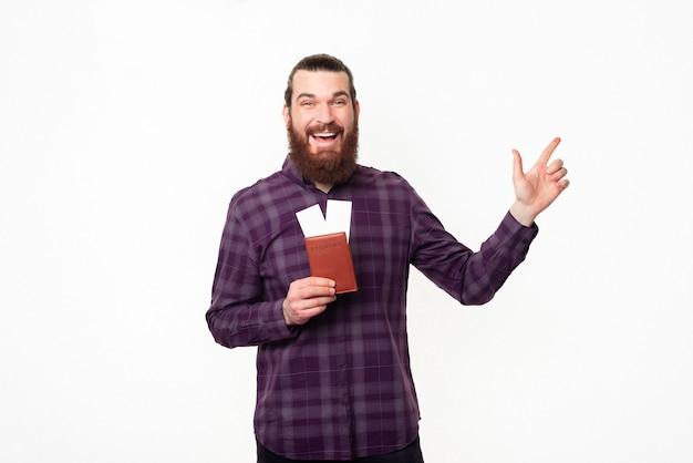 Jovem feliz com barba e camisa quadriculada segurando ingressos e apontando para longe