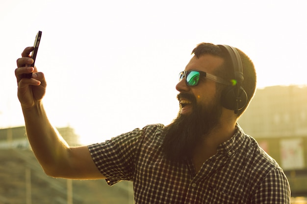 Jovem feliz com barba longa, tomando uma selfie com o telefone na rua