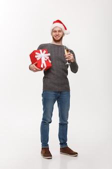 Jovem feliz com barba segurando um presente e champanhe comemorando o natal em branco