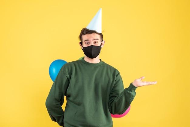 Jovem feliz com boné de festa escondendo balões coloridos atrás das costas em pé no amarelo