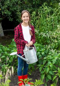 Jovem feliz com botas de borracha vermelha regando legumes no jardim