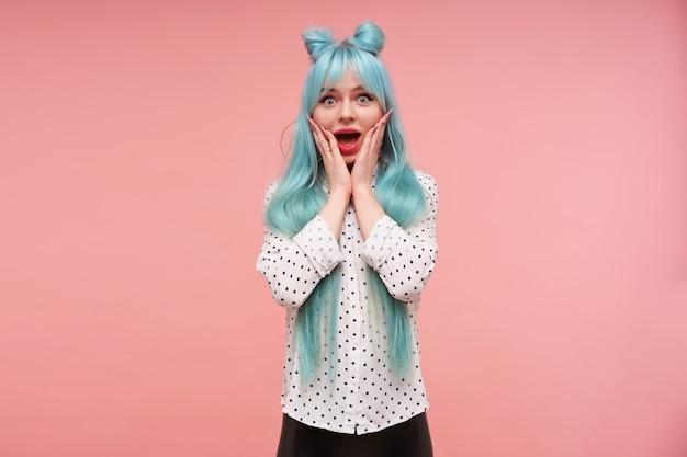 Jovem feliz com cabelos azuis, linda mulher, olhos arredondados e segurando o rosto com as palmas das mãos levantadas enquanto olha, usando roupas elegantes enquanto posa