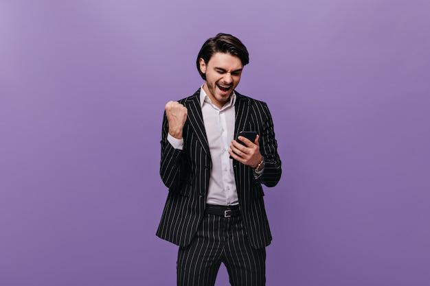 Jovem feliz com cabelos castanhos, camisa branca e terno listrado preto, emocionalmente olhando para o telefone, regozijando-se e posando contra a parede violeta pastel