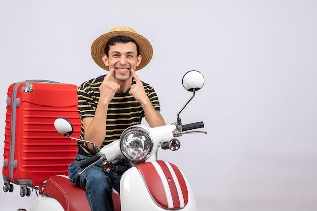 Jovem feliz com chapéu de palha na motocicleta apontando para o sorriso de frente