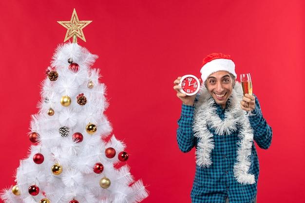 Jovem feliz com chapéu de papai noel e mostrando uma taça de vinho e um relógio em pé perto da árvore de natal no vermelho
