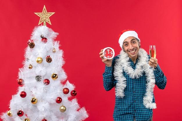 Jovem feliz com chapéu de papai noel e segurando uma taça de vinho e um relógio em pé perto da árvore de natal no vermelho