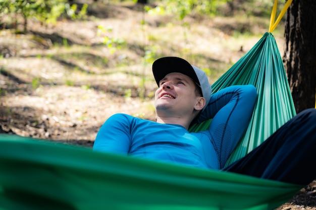 Jovem feliz com chapéu relaxando do lado de fora em uma rede na floresta