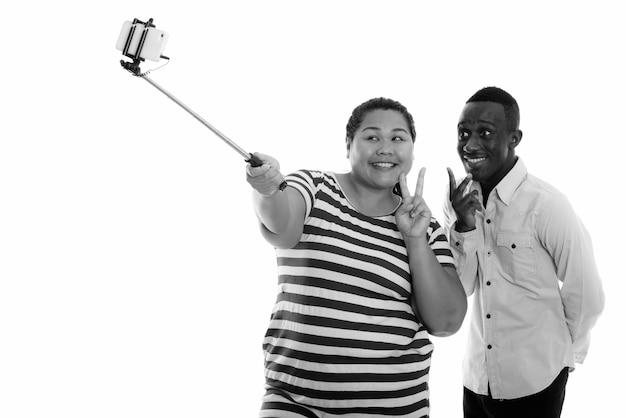 Jovem feliz com excesso de peso, mulher asiática e jovem africano como casal tirando uma selfie junto com o telefone no stick de selfie
