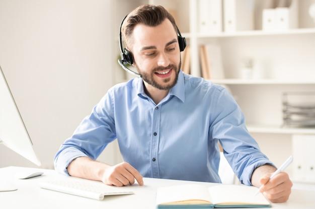 Jovem feliz com fone de ouvido sentado na mesa, consultando clientes e fazendo anotações de trabalho no caderno
