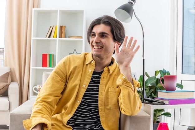 Jovem feliz com roupas casuais olhando de lado acenando com a mão sorrindo alegremente, sentado na cadeira na sala iluminada