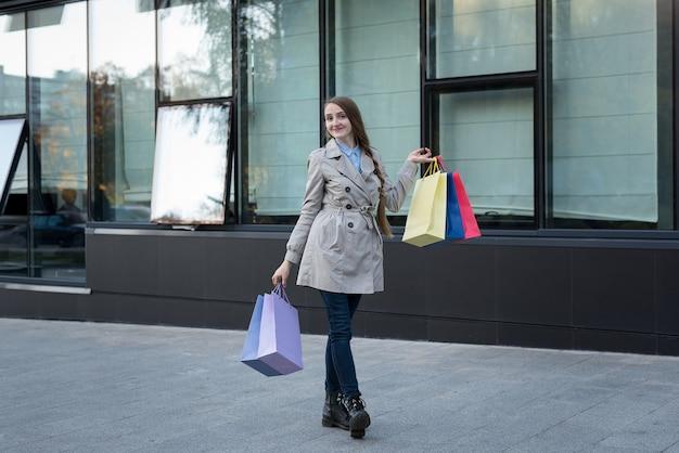 Jovem feliz com sacos coloridos perto de shopping. shopaholic