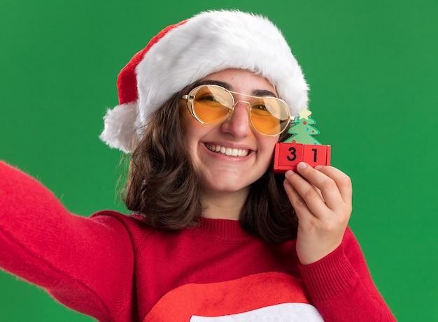Jovem feliz com suéter de natal com chapéu de papai noel e óculos segurando cubos de brinquedo com encontro de ano novo com um grande sorriso no rosto em pé sobre a parede verde