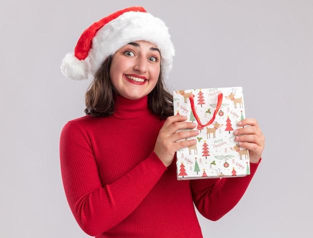 Jovem feliz com suéter vermelho e chapéu de papai noel segurando um saco de papel colorido com presentes de natal, olhando para a câmera com um sorriso no rosto em pé sobre um fundo branco