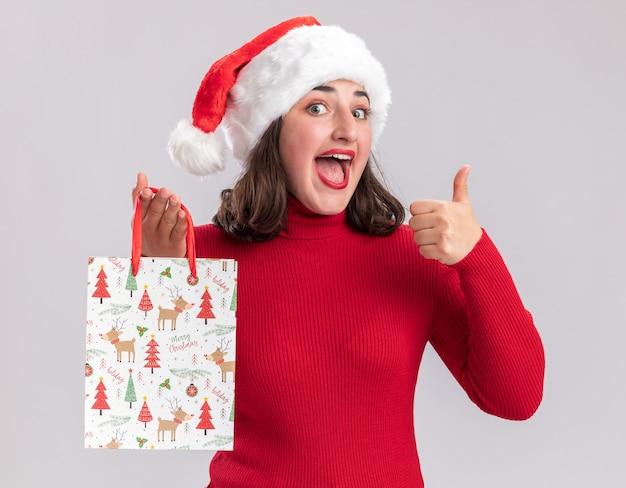 Jovem feliz com suéter vermelho e chapéu de papai noel segurando um saco de papel colorido com presentes de natal, olhando para a câmera com um sorriso no rosto mostrando os polegares em pé sobre um fundo branco