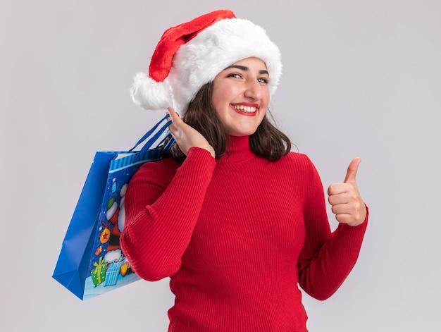 Jovem feliz com suéter vermelho e chapéu de papai noel segurando um saco de papel colorido com presentes de natal, olhando para a câmera e sorrindo mostrando os polegares em pé sobre um fundo branco