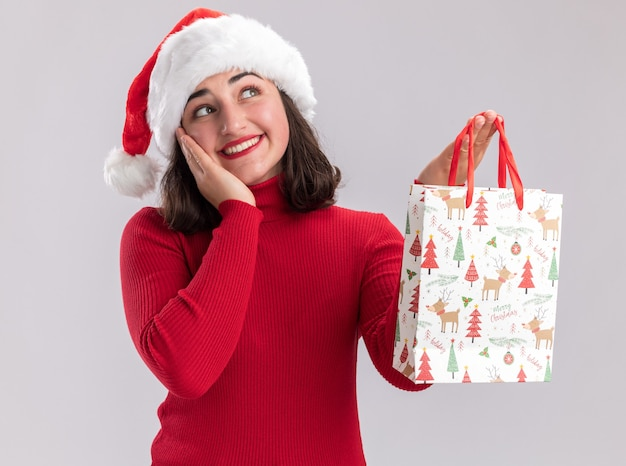 Jovem feliz com suéter vermelho e chapéu de papai noel segurando um saco de papel colorido com presentes de natal olhando para cima com um sorriso no rosto em pé sobre um fundo branco