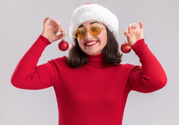 Jovem feliz com suéter vermelho e chapéu de papai noel usando óculos segurando bolas de natal, olhando para a câmera, sorrindo amplamente em pé sobre um fundo branco