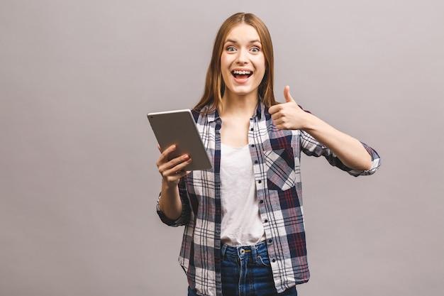 Jovem feliz com tablet digital aparecendo polegar.
