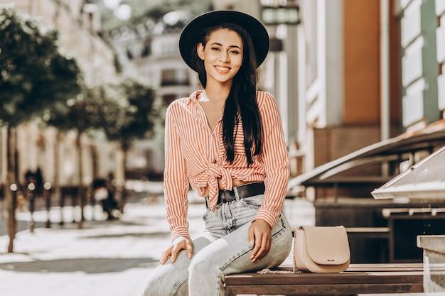 Jovem feliz com um chapéu sentada na rua em um dia ensolarado