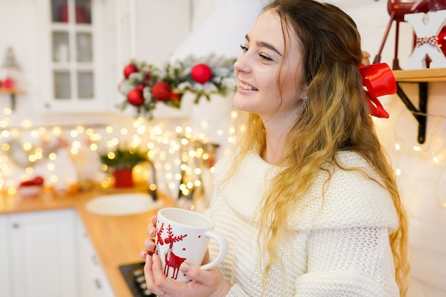 Jovem feliz com uma xícara de café na cozinha decorada de natal
