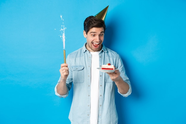 Jovem feliz comemorando aniversário com chapéu de festa, segurando um bolo de aniversário e sorrindo, em pé sobre um fundo azul