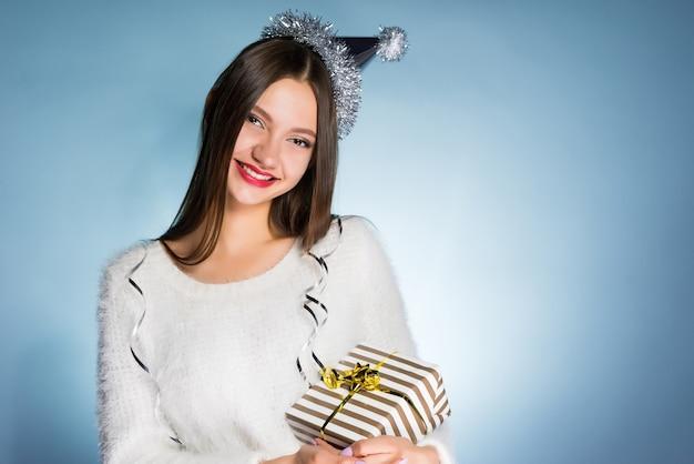 Jovem feliz comemorando o ano novo segurando um presente e sorrindo