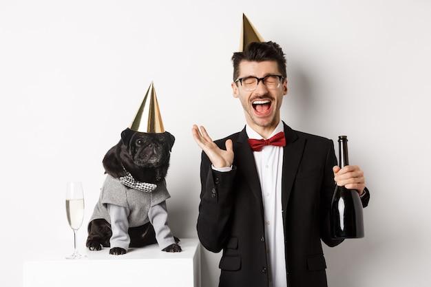 Jovem feliz comemorando o feriado com cachorro bonito, segurando champanhe e sorrindo, pug e proprietário vestindo fantasias de festa, fundo branco.