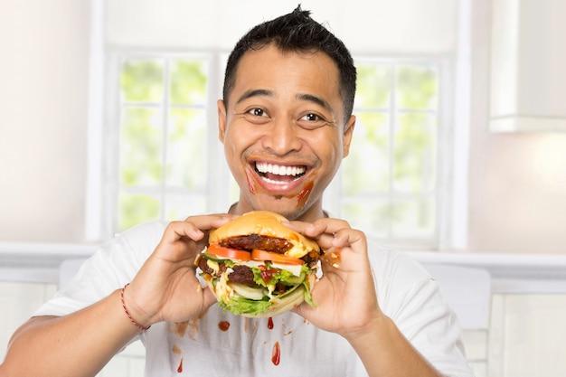 Jovem feliz comendo um hambúrguer grande