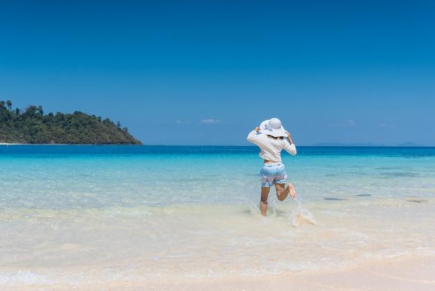 Jovem feliz correndo para a praia em koh mook da tailândia