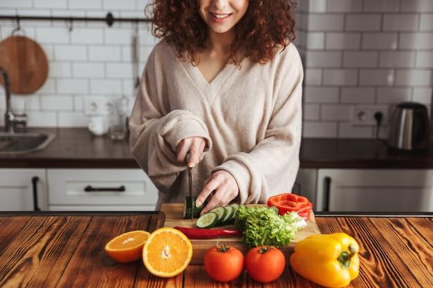 Jovem feliz cortando legumes frescos enquanto cozinha uma salada no interior da cozinha em casa