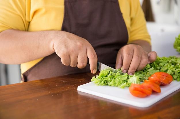 Jovem feliz cozinhando sua refeição