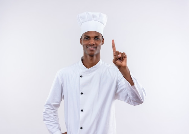 Jovem feliz cozinheira afro-americana com uniforme de chef aponta isolado na parede branca