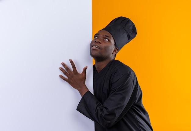 Jovem feliz cozinheira afro-americana com uniforme de chef fica atrás e coloca a mão na parede branca, olhando para cima, isolada no espaço laranja com espaço de cópia