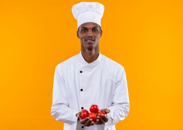 Jovem feliz cozinheira afro-americana com uniforme de chef segurando batatas com as duas mãos isoladas na parede laranja