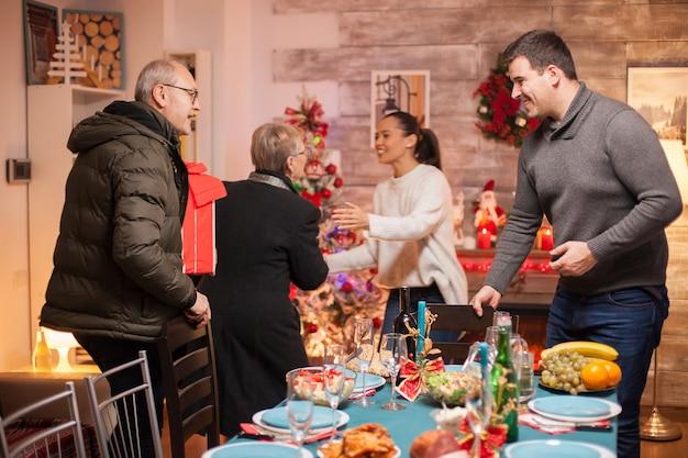 Jovem feliz cumprimentando seu pai para o jantar de natal em família.