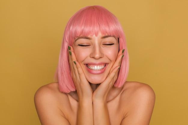 Jovem feliz de aparência agradável com cabelo curto rosa segurando o rosto com as palmas das mãos levantadas enquanto posa sobre uma parede de mostarda, mantendo os olhos fechados enquanto sorri amplamente