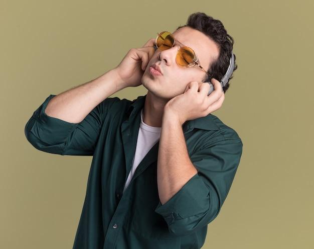 Jovem feliz de camisa verde, usando óculos e fones de ouvido, curtindo sua música favorita em pé sobre a parede verde